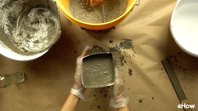 Molding concrete for DIY concrete tabletop tiki torches out of used glass bottles.