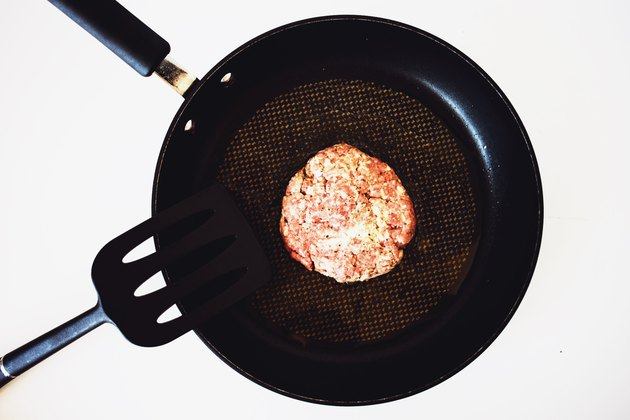 A burger patty in a frying pan.