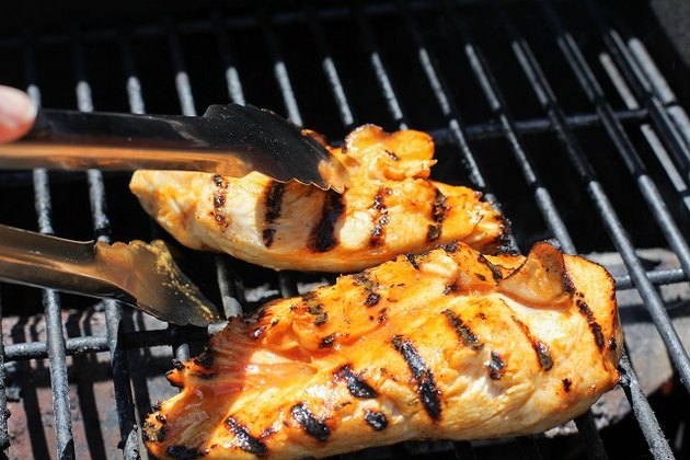 Chicken being flipped on a grill
