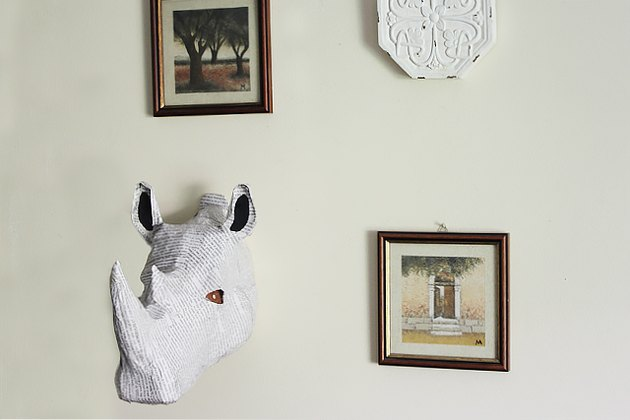 rhino bust hanging on wall with picture frames