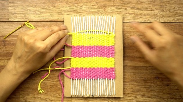 Weaving DIY coasters on a cardboard loom.