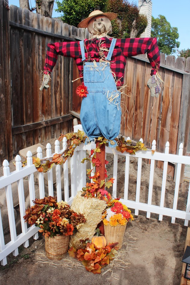 scarecrow on a sign post in a garden