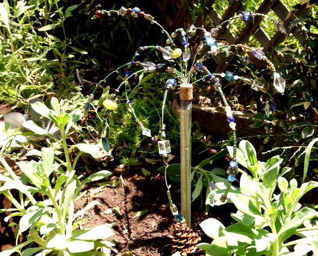 DIY glass beaded garden sparkler in soil among plants.