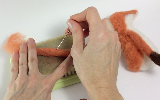 Female hands needle felting a thin limb of wool roving