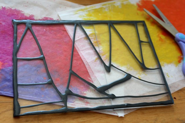 A painted acrylic frame atop two multicolored melted crayon pages with scissors