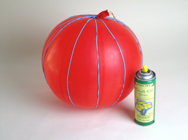 A balloon with a can of cooking oil.