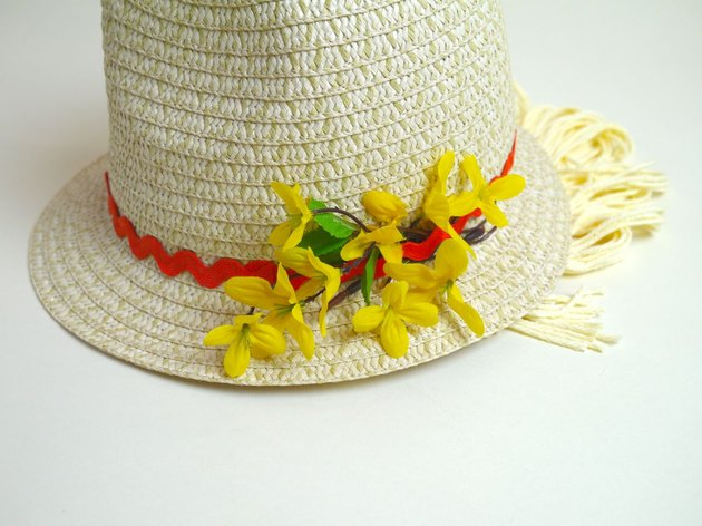 Yellow silk flowers glued to the side of the hat in a cluster.