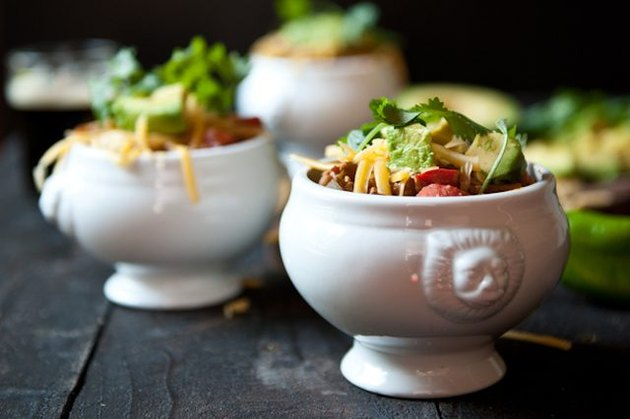 Fresh batches of chili served in porcelain dishes, topped with colorful garnishes.