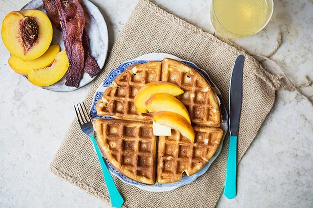A waffle topped with sliced peaches