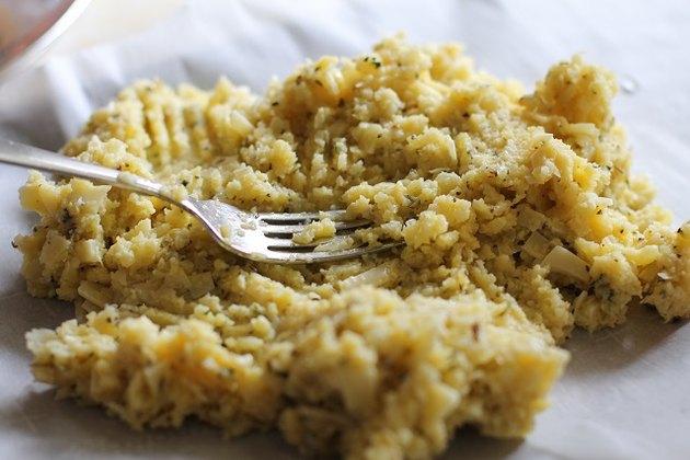 Fork spreading cauliflower mixture onto baking sheet.