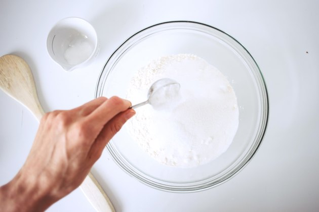 Hand spooning dry ingredients into a glass bowl.