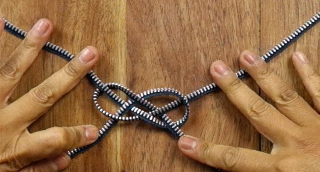 Tying a knot to make a knotted bracelet from a zipper.