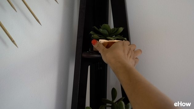 Placing a faux succulent on a corner shelf.