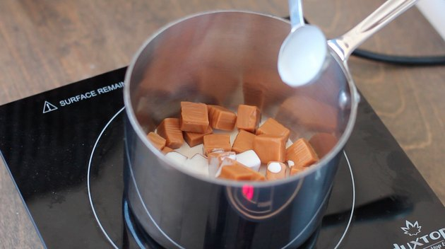 Adding cream to caramel candies in saucepan.