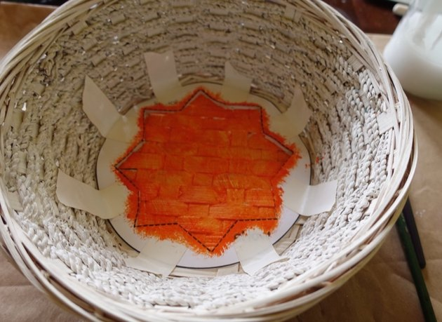 Using stencil to paint DIY desert-style baskets.