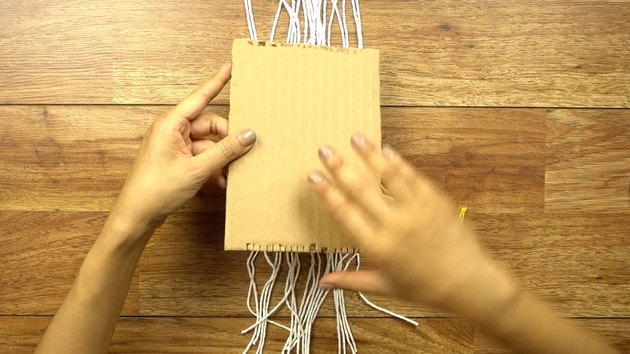 Removing weaving from cardboard loom.