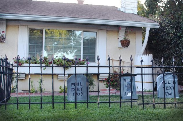 A faux rusted fence surrounding fake tombstones