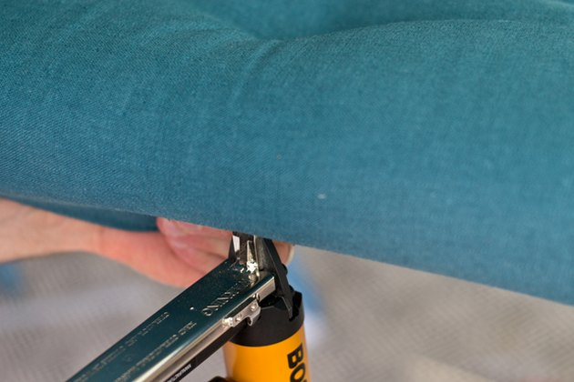 Secure the sides of the fabric underneath the board with the staple gun.