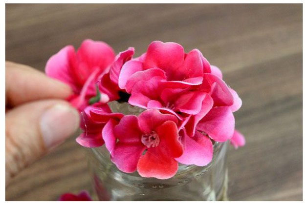 Gluing silk flowers to jar.