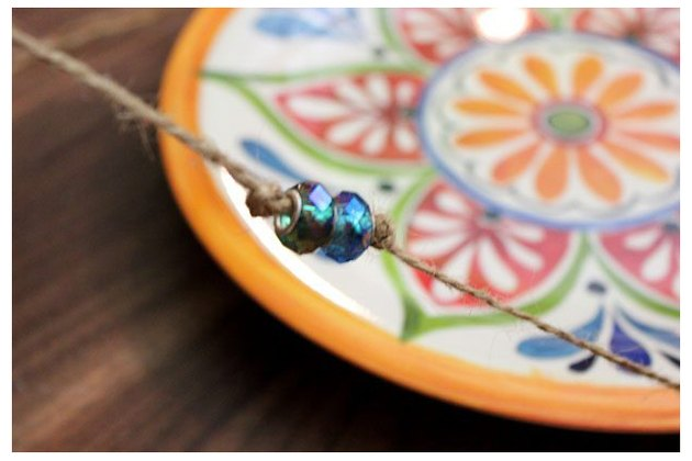 Add beads to string on plate.