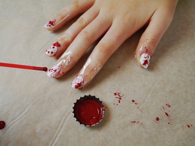 A cocktail straw splattering red polish over the white nails.