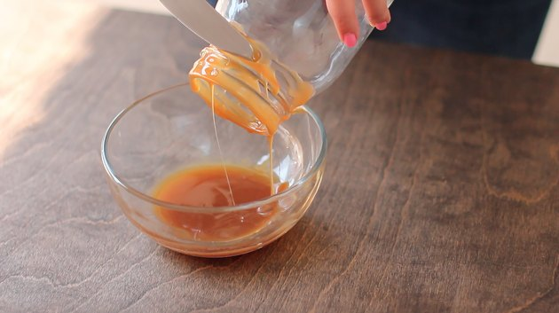 Dipping the rim of a Mason jar in caramel sauce.