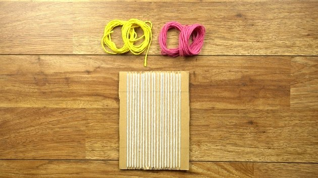 Cut yarn for DIY coasters on a cardboard loom.