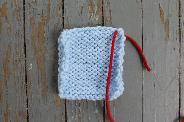 Inserting the yarn at the edge of the knitting for whip stitch