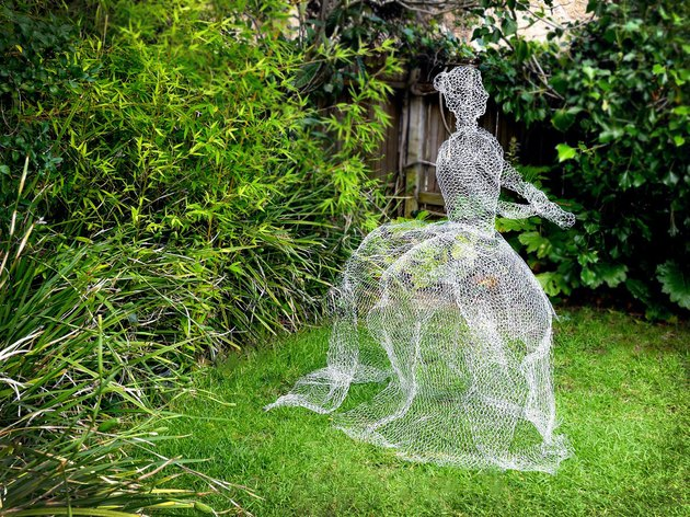 A life sized chicken wire ghost appears barely there in a garden.