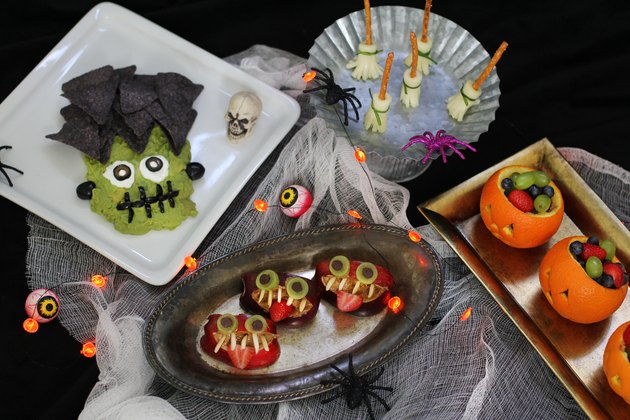 Four healthy Halloween snacks: Frankenstein guacamole, witch's broom cheese sticks, apple monsters, jack o'lantern fruit cups