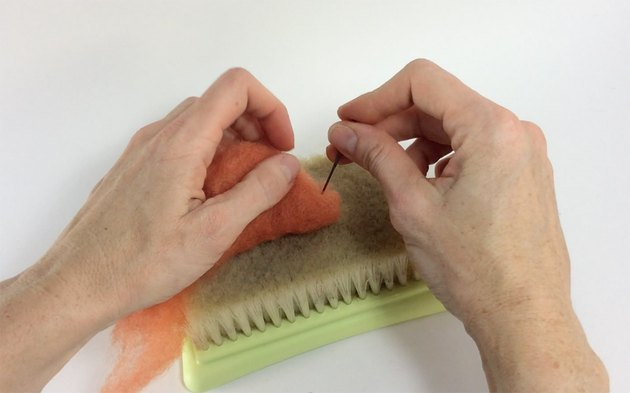 Female hands needle felting orange roving on a felting pad