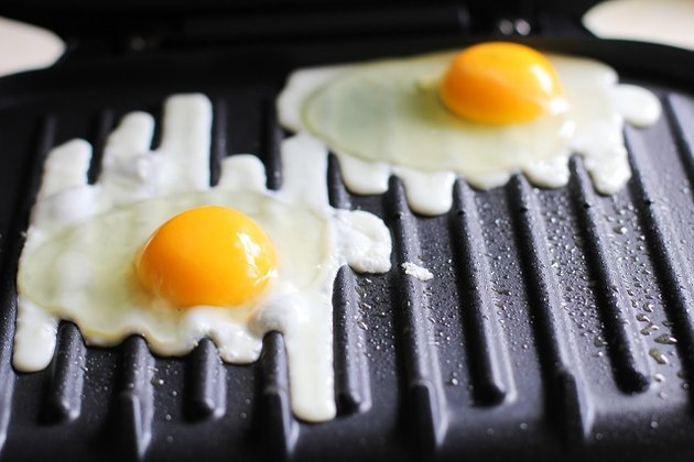 Sunny-side-up eggs cooking on a George Foreman Grill.