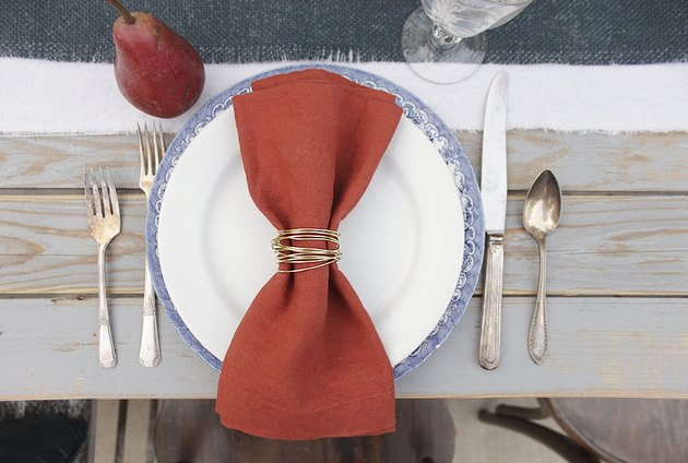 Gold wire napkin rings being used with rust-colored napkins on a fall table.