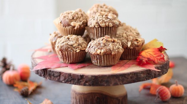 Streusel-topped muffins displayed on a wooden pedestal