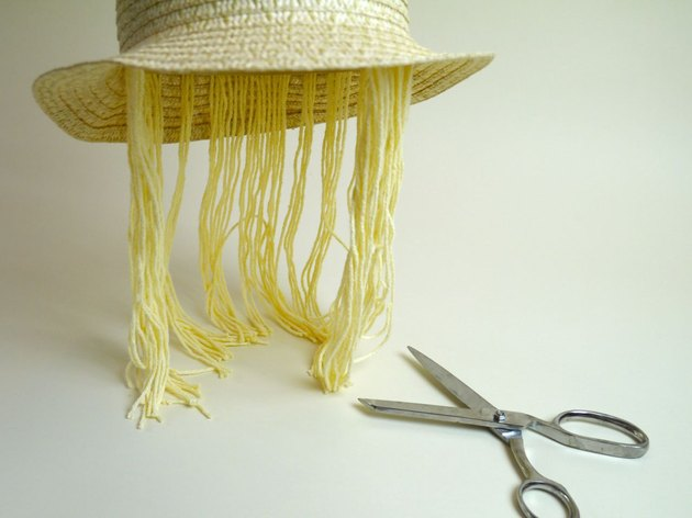 The hat with the trimmed yarn and a pair of scissors.