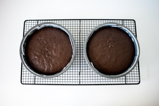 Two cake pans cooling on a rack.