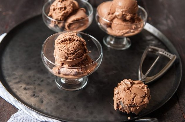 Three bowls of ice cream on a silver tray with an ice cream scoop