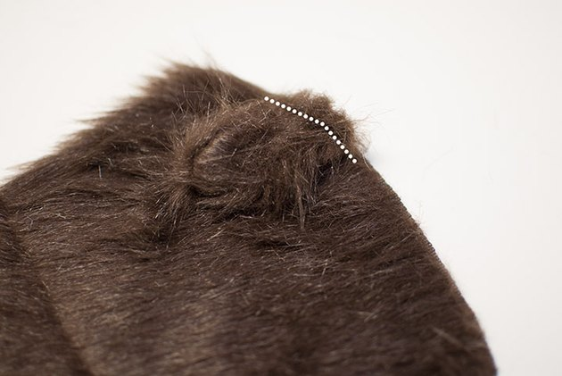 Sew the pony tail to the hood.