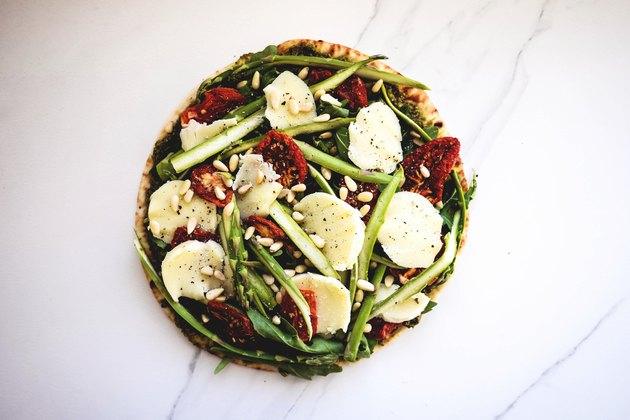 Asparagus, Sun-dried Tomato, Pesto and Arugula Pizza ready for baking.