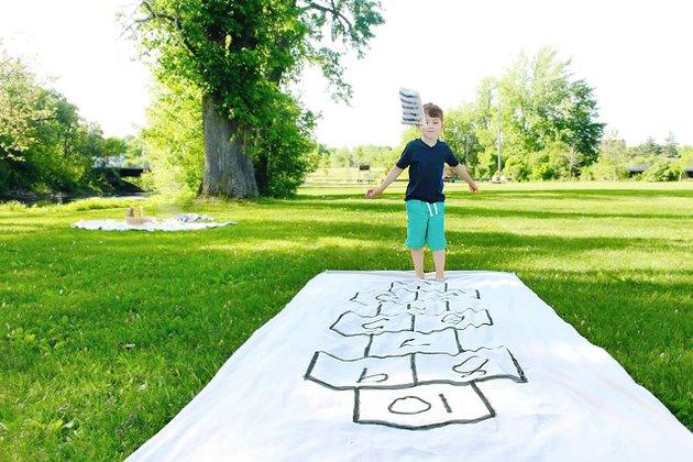 little boy playing on a portable DIY hopscotch board