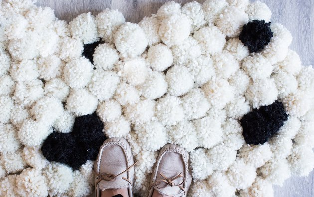 Women's shoes seen standing on pom-pom rug