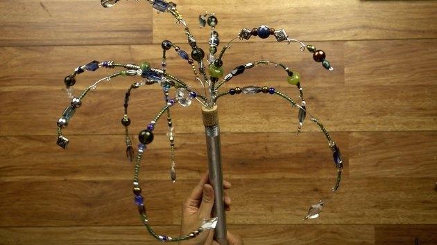 Inserting beaded wires into cork for DIY glass beaded garden sparkler.