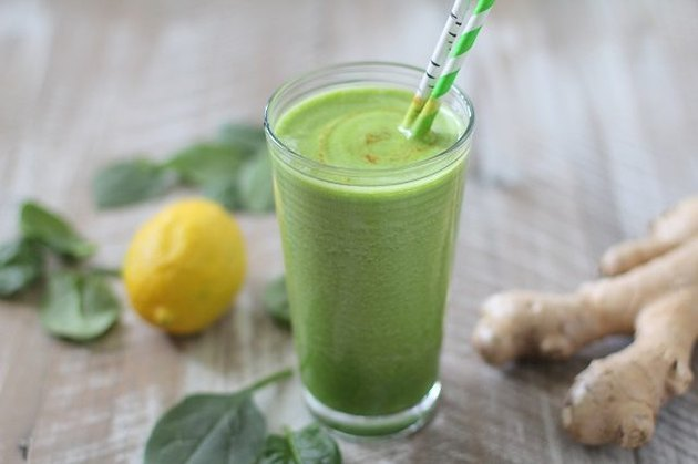 A glass of a green detoxifying smoothie next to spinach leaves, ginger and a lemon.