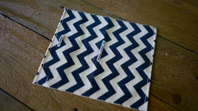 Buttonholes created on fabric for DIY dog waste bag dispenser