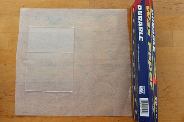 A sheet of wax paper with a clear acrylic picture frame laying directly on the wax paper
