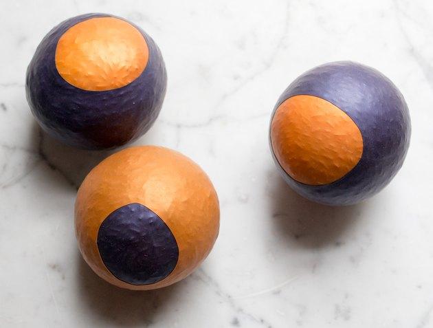 Three purple and gold homemade stress balls