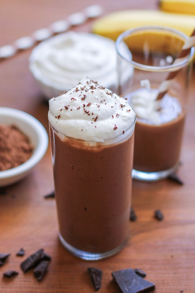 A glass with chocolate shake and whipped cream on top.