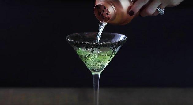 straining apple martini into martini glass