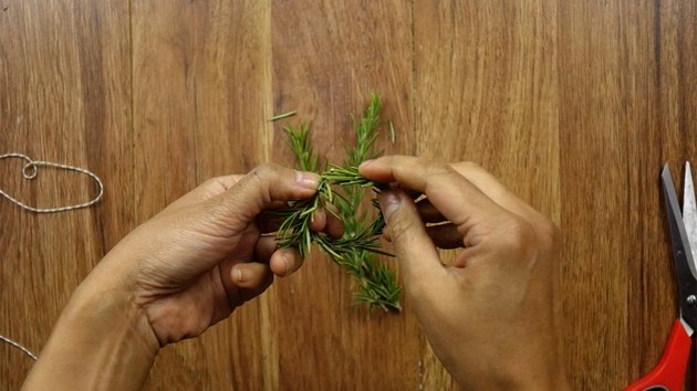 Bending rosemary sprig to create a mini Christmas wreath for DIY gift tag.