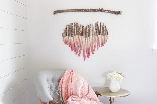 A wooden wall hanging in the shape of a heart hanging over a chair and table